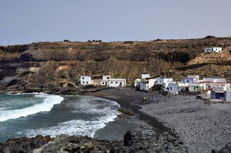 El Puerte de Los Molinos, Fuerteventura, Spain - April 01, 2017: Unidentified people, restaurant and homes on the tiny beach on west coast of the Canary island