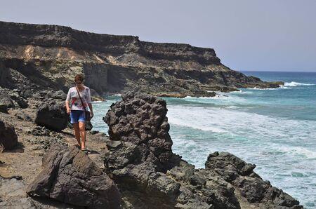 Fuerteventura, Spain - April 01, 2017: Unidentified woman walking along rocky coast in El Puerte de Los Molinos, Editorial