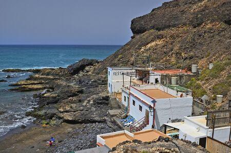 Fuerteventura, Spain - April 01, 2017: Unidentified people and buildings on beach in El Puerte de Los Molinos on atlantic ocean Editorial