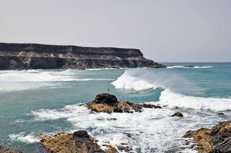 Spain, Canary Island, Fuerteventura, coast and surfer in El Puerte de Los Molinos,