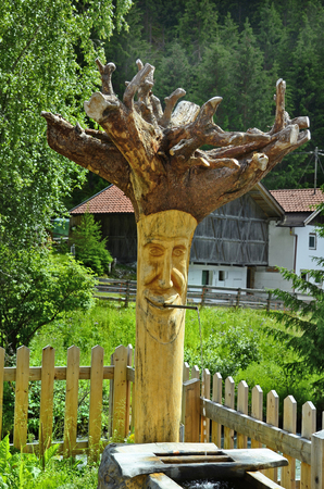 well made: Wiesle, Tyrol, Austria - June 20, 2016: Funny drinking water well made from trunk tree in Pitztal valley Editorial