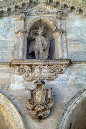 Monte San Angelo, Italy - June 16, 2007: Sculpture of Saint Michel aka San Michele on front of the pilgrimage church in Puglia