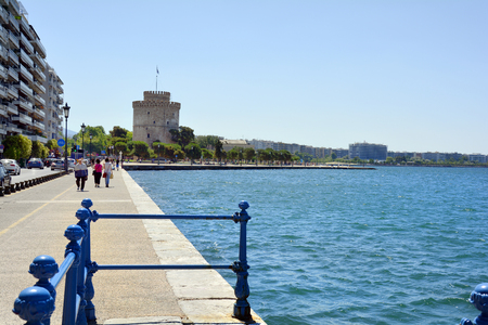 Thessaloniki, Greece - June 09, 2017: Unidentified people and White Tower on shore of Aegean sea