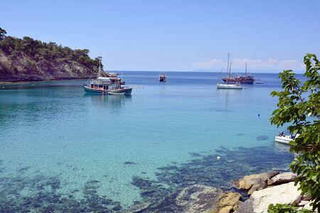 Aliki, Greece - June 10, 2017: Unidentified people and ships on Aliki beach, preferred travel destination on Thassos island