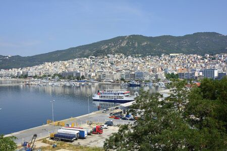 Kavala, Greece - June 15, 2017: Cityscape with harbor, cargo and passender terminal and ferry in the city on Aegean sea Editorial