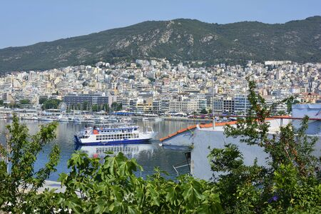 Kavala, Greece - June 15, 2017: Cityscape with harbor and ferry in the city on Aegean sea