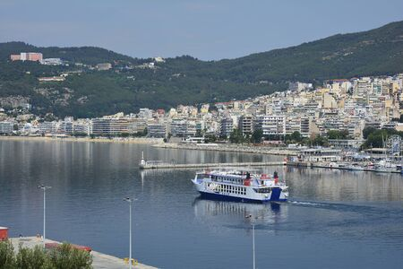 Kavala, Greece - June 15, 2017: Ferry leaving harbor of the city on Aegean sea, hospital building on hill Editorial