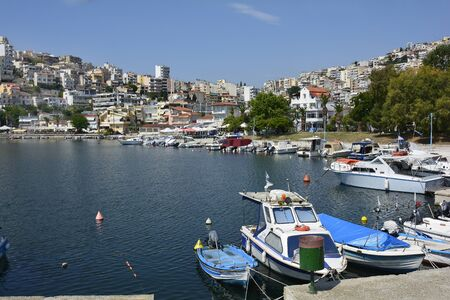 Kavala, Greece - June 15, 2017: Restaurants and different boats in tiny harbor Perigiali on Aegean sea