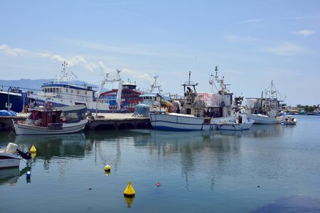 Keramoti, Greece - June 15, 2017: Trawler and fishing boats in the harbor of the village in East Macedonia, Thassos island in background