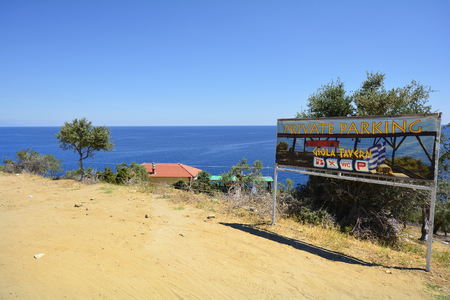 Thassos Island, Greece - June 10, 2017: Signpost to tavern on preferred natural rock pool Giola on the coast on Aegean sea Editorial