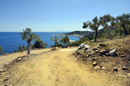 Thassos Island, Greece - June 10, 2017: Unidentified people on unsealed road to tavern and natural rock pool Giola on the coast on Aegean sea, holy Mount Athos in background