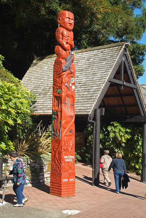 Rotorua, New Zealand - March 12, 2005: Unidentified people by entrance with Maori sculpture into Waitoma Caves, preferred cave to visit glowormes on North Island