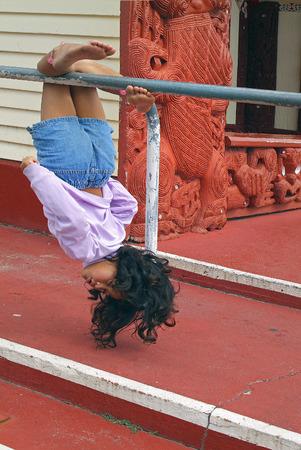 Rotorua, New Zealand - March 12, 2005: Unidentified little girl do gymnastics in front of Maori building