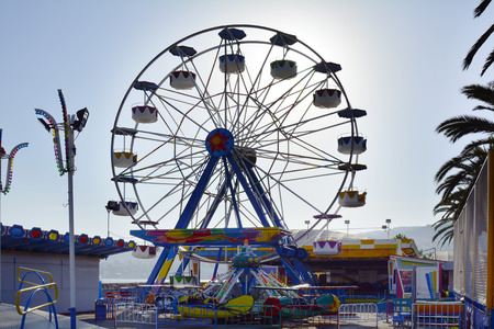 Kavala, Greece - September 17, 2015: Amusement park with roundabout and ferris wheel in the city in Eastmacedonia Editorial