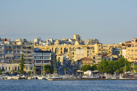 Kavala, Greece - June 12, 2017: Cityscape with medieval aqeduct Kamares, harbor, ships and buildings in the city in Eastmacedonia