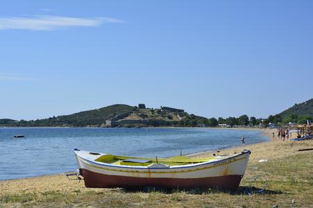 Kavala, Greece - June 13, 2017: Unidentified people and boat on beach of Nea peramos with byzantine castle Anaktoroupoli