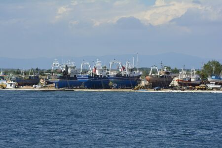 Keramoti, Greece - June 10, 2017: Different ships on dry dock in wharf of the village on Aegean sea in Eastmacedonia