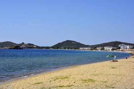 Kavala, Greece - June 13, 2017: Unidentified people on beach of Nea peramos with byzantine castle Anaktoroupoli