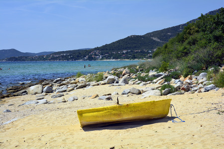 Kavala, Greece - June 14, 2017: Unidentified people and yellow rowing boat on sandy Palio beach on Aegean sea