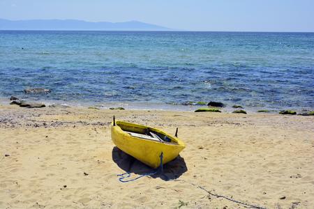 Greece, Kavala, yellow rowing boat on beach of Aegean sea, Thassos island on horizon