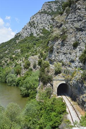 Griekenland, Nestos River Gorge met tunnel van Drama - Xanthi-spoorlijn en voetpad langs de rivier Stockfoto