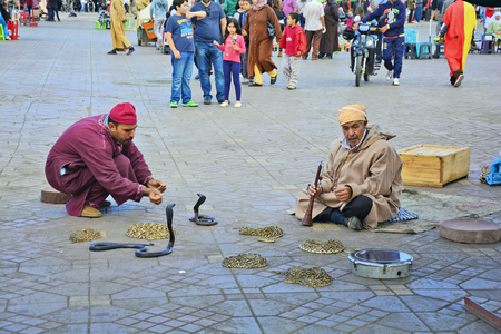 Marrakesh, Morocco - November 22nd 2014: Unidentified people and snake charmer on Djemaa el-Fna square, tourist attraction and tradition