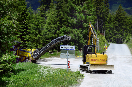 Piller, Austria - June 22, 2016: Unidentified worker on milling machine and mechanical digger for road construction