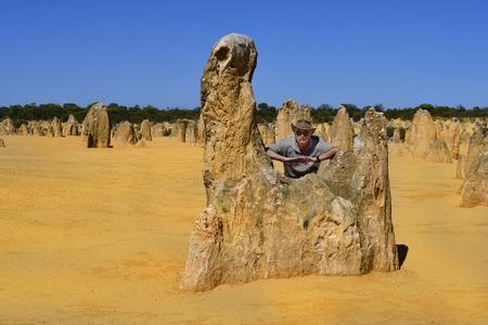 Cervantes, WA, Australia - November 23, 2017: Man on rock of The Pinnacles in Nambung National Park, preferred tourist attraction and natural landmark Editorial