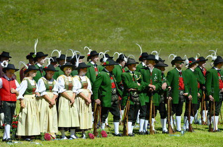 Feichten, Tyrol, Austria - June 22, 2014: Unidentified folklore group, Tyrolean gun men in traditional outfit and weapons by field mass in Kaunertal valley