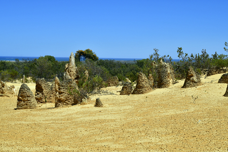 Australië, WA, de Toppen in het Nationale Park van Nambung, voorkeurstoeristische attractie en natuurlijk oriëntatiepunt, Indische Oceaan op achtergrond