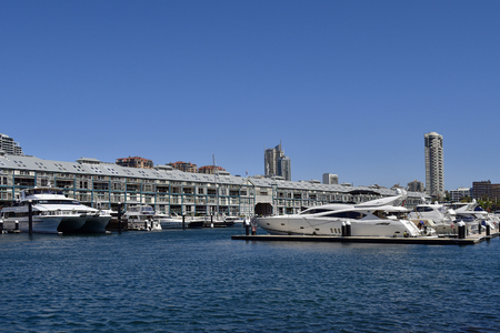 Sydney, NSW, Australia - October 31, 2017: Different yachts and boats on Woolomooloo Finger Wharf, Horizon apartments building in background right