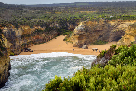 Unidentified people on beach of Loch Ard Gorge on Great Ocean Road in Port Campbell National Park
