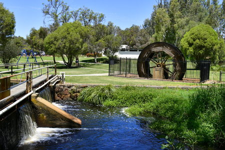 Gingin, WA, Australia: Unidentified people and old water wheel in public Granville park in the village of Western Australia Stock Photo