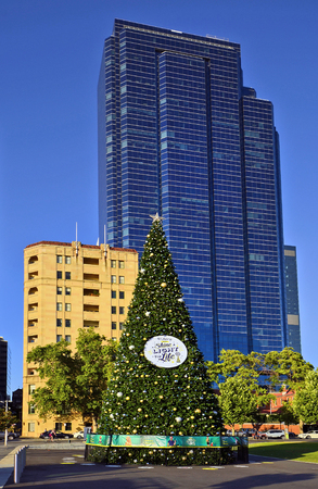 Pert, WA, Australia - November 27, 2017: Decorated Christmas tree on Elizabeth quay with skysraper and old building behind