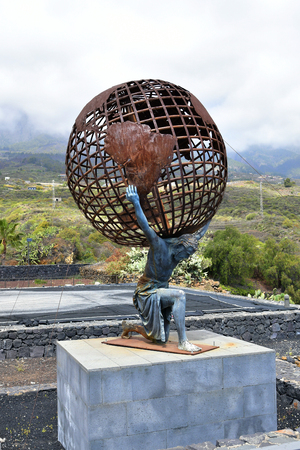 Guimar, Canary Islands, Spain - April 06, 2018: Sculpture with Titan Atlas carry the world on his shoulders, historic figure from Greek mythology Sajtókép