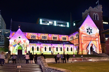 Perth, WA, Australia - November 30, 2017: Unidentified people watching illuminated St. Georges church, with video operated Christmas scenes