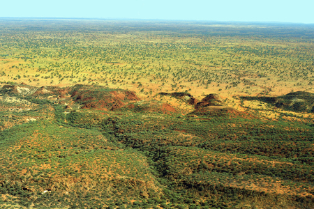 Australia, NT, aerial view from arid landscape south of Alice Springs with McDonnel range on horizon Stock Photo