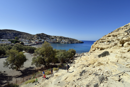 Matala, Greece - October 07, 2018: Unidentified people by sightseeing of ancient tombs in the archaeological site in the south of Crete, a preferred location for vacation and former hippie colony