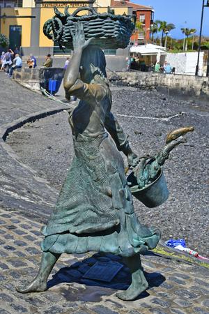Tenerife, Canary Islands, Spain - April 03, 2018: Bronze sculpture of a fishmonger from sculptor Julio Neto  in Puerto de la Cruz 新聞圖片