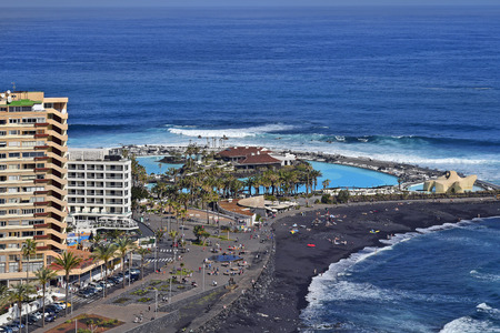Tenerife, Canary Islands, Spain - April 01, 2018: Unidentified people on promenade and beach with volcanic black sand on Atlantic ocean, pool landscape named Lago Martianez with Monumento del Mar Stock Photo - 115124608