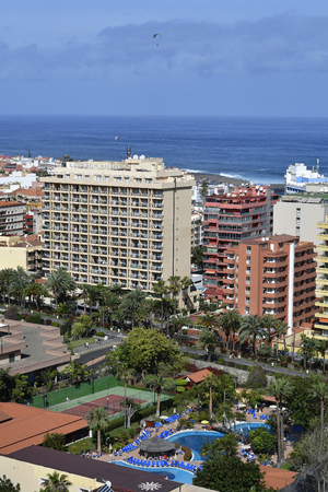 Tenerife, Canary Islands, Spain - April 01, 2018: cityscape with different buildings, hotel, pool and tennis court in Puerto de la Cruz on Atlantic ocean, para gliders in sky Editorial