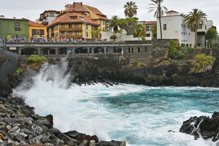 Tenerife, Canary Islands, Spain - April 01, 2018: Unidentified people watching the surf on promenade in Puerto de la Cruz