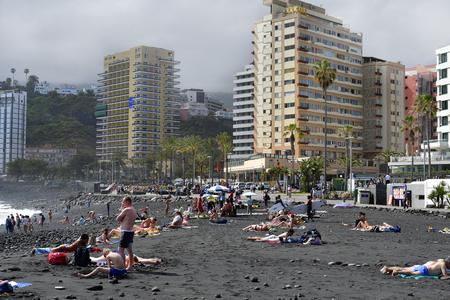 Tenerife, Canary Islands, Spain - April 01, 2018: Unidentified people on sandy beach in Puerto de la Cruz Editorial