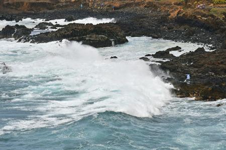 Tenerife, Canary Islands, Spain - April 04, 2018: Unidentified people on coast of Punta de Teno watching breakers in rough sea Stock Photo