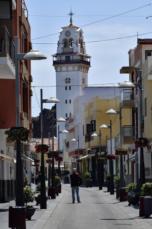 Tenerife, Canary Islands, Spain - April 06, 2018: Unidentified people in pedestrian zone with bell tower of pilgrimage church in village Candelaria