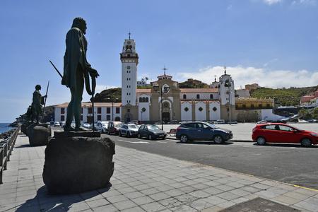 Tenerife, Canary Islands, Spain - April 06, 2018: Bronze sculptures made from sculptor Jose Abad and Basilica de Nuestro Senora de Candelaria in village Candelaria