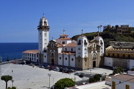 Tenerife, Canary Islands, Spain - April 06, 2018: Basilica de Nuestro Senora de Candelaria and bronze sculpture on Atlantic ocean in village Candelaria