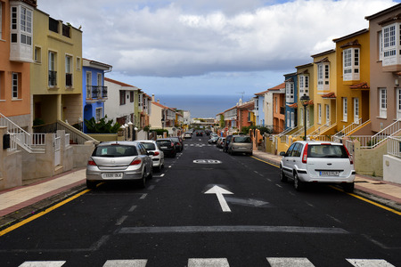 Tenerife, Canary Island, Spain - April 07, 2018: Colorful terraced houses in street, all look similar in the mountain village La Orotava with Atlantic ocean in background