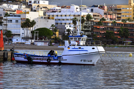 Tenerife, Canary Islands, Spain - April 10, 2018: Trawler, beach and buildings in Los Cristianos