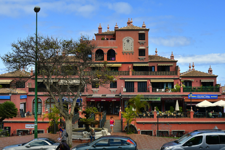 Tenerife, Canary Islands, Spain - April 12, 2018: Unidentified people and building with sun dial and different shops in Puerto de la Cruz